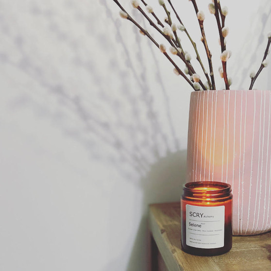 A lit Selene candle is in the forefront of the image, with a pink vase and dried cotton flowers in the background. Both are on top of a wooden surface.