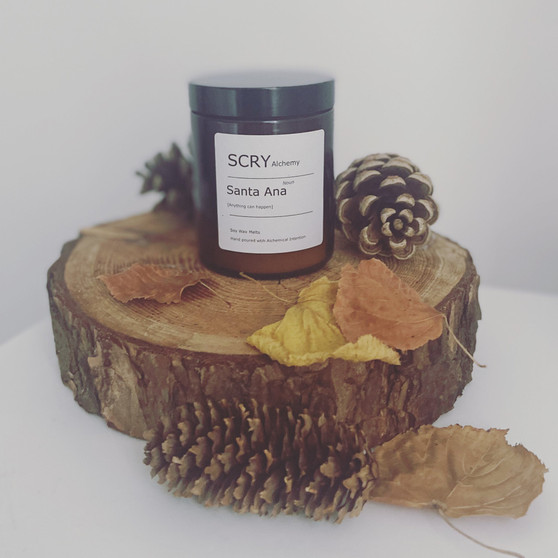 A Santa Ana candle is placed on top of a wooden tree stump, with autumn leaves and acorns placed around it. The photo is taken indoors, on a white background.