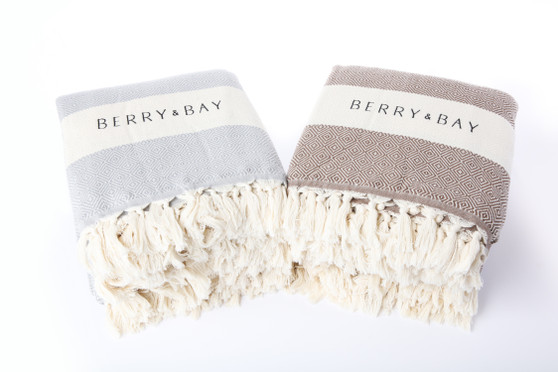 Two folded up blankets sit side by side on a white backdrop. Both have the Berry & Bay logo on them.