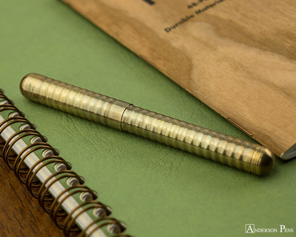 Kaweco Liliput Fountain Pen - Eco Brass Wave - Closed on Notebook
