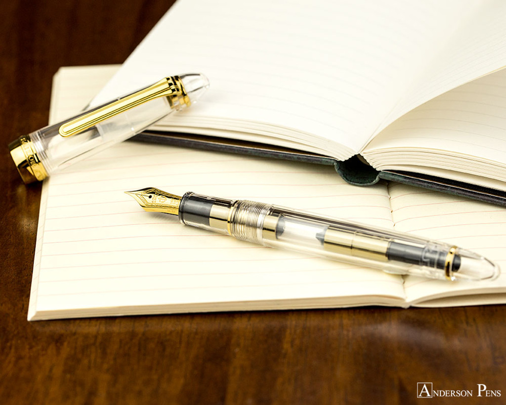 Sailor 1911 Standard Fountain Pen - Transparent with Gold Trim - Open on Notebook