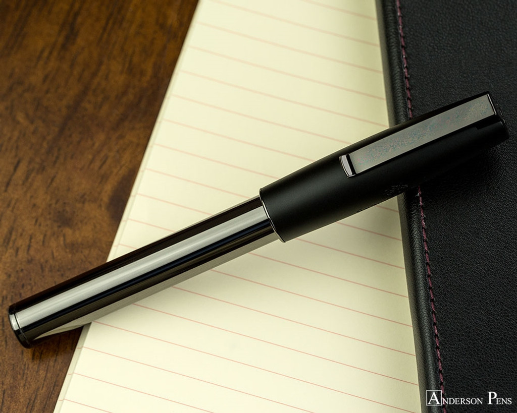 Faber-Castell Loom Rollerball - Gunmetal Polished - Closed on Notebook