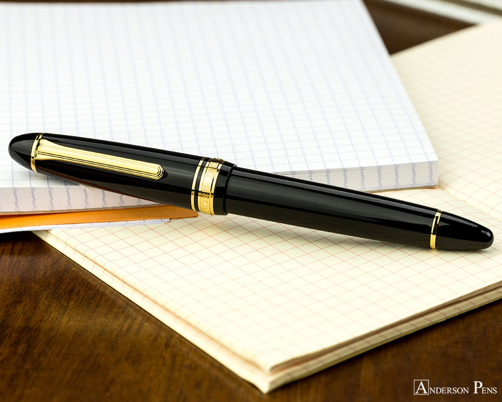 Sailor 1911 Large Fountain Pen - Black with Gold Trim - Closed onNotebook