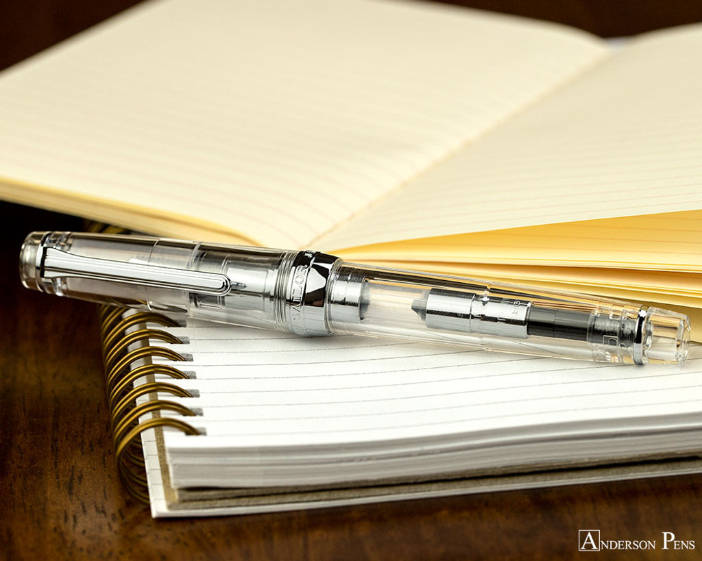 Sailor Pro Gear Fountain Pen - Transparent with Rhodium Trim - Closed on Notebook