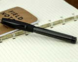 Faber-Castell Essentio Black Carbon Fountain Pen - Closed on Notebook