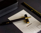 ystudio Resin and Brass - Black Rollerball Pen - Open on Postcard