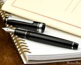 Sailor Pro Gear Slim Fountain Pen - Black with Rhodium Trim - Open on Notebook