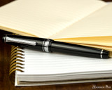 Sailor Pro Gear Slim Fountain Pen - Black with Rhodium Trim - Closed on Notebook