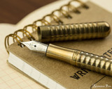Kaweco Liliput Fountain Pen - Eco Brass Wave - Open on Notebook