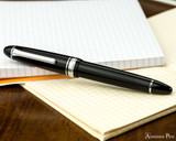 Sailor 1911 Large Fountain Pen - Black with Rhodium Trim - Closed on Notebook