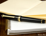 Sailor Pro Gear Fountain Pen - Black with Gold Trim - Closed on Notebook