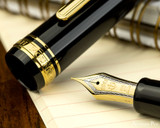 Sailor Pro Gear Fountain Pen - Black with Gold Trim - Nib on Notebook