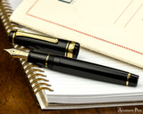 Sailor Pro Gear Fountain Pen - Black with Gold Trim - Open on Notebook