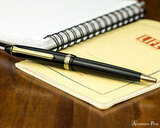 Sailor 1911 Standard Ballpoint - Black with Gold Trim - On Notebook