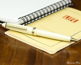 Sailor 1911 Standard Ballpoint - Ivory with Gold Trim - Open on Notebook