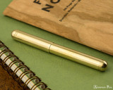 Kaweco Liliput Fountain Pen - Brass - Closed on Notebook