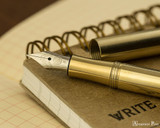 Kaweco Liliput Fountain Pen - Brass - Nib on Notebook