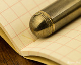 Kaweco Liliput Fountain Pen - Brass - Barrel End on Notebook