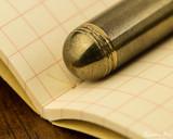 Kaweco Liliput Fountain Pen - Brass - Barrel End on Notebook