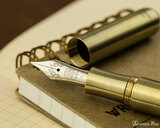 Kaweco Liliput Supra Fountain Pen - Brass - Nib on Notebook