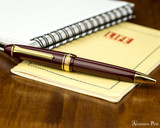 Sailor 1911 Large Ballpoint - Maroon with Gold Trim - On Notebook