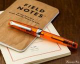 Sailor Professional Gear Slim Fountain Pen - Transparent Orange with Rhodium Trim - Closed on Field Notes