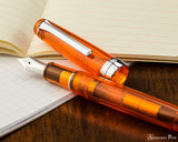 Sailor Professional Gear Slim Fountain Pen - Transparent Orange with Rhodium Trim - Open on Notebook