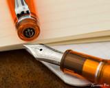Sailor Professional Gear Slim Fountain Pen - Transparent Orange with Rhodium Trim - Nib on Notebook