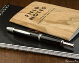 Pilot Vanishing Point Fountain Pen - Black with Rhodium Trim - Closed on Notebook