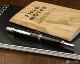 Pilot Vanishing Point Fountain Pen - Black with Rhodium Trim - Closed on Notebook