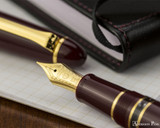 Sailor 1911 Realo Fountain Pen - Maroon with Gold Trim - Nib on Notebook
