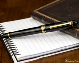 Sailor 1911 Large Fountain Pen - Black with Gold Trim - Resting on Notebook
