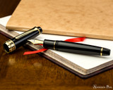 Sailor Pro Gear King of Pen Fountain Pen - Black with Gold Trim - Open on Notebook