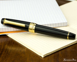Sailor Pro Gear King of Pen Fountain Pen - Black with Gold Trim - Closed on Notebook