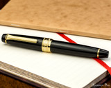 Sailor Pro Gear King of Pen Fountain Pen - Black with Gold Trim - Closed on Notebook 2