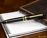 Sailor 1911 Realo Fountain Pen - Black with Gold Trim - Closed on Notebook
