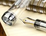 Sailor Pro Gear Fountain Pen - Transparent with Rhodium Trim - Nib on Notebook