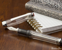 TWSBI Vac 700R Fountain Pen - Clear - Open on notebook
