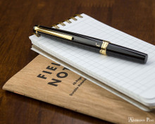 Pilot E95S Fountain Pen - Black - Closed on Notebook