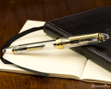 Sailor 1911 Standard Fountain Pen - Transparent with Gold Trim - Closed on Notebook