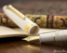 Sailor 1911 Large Fountain Pen - White with Gold Trim - Nib on Notebook