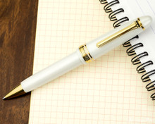 Sailor 1911 Large Ballpoint - White with Gold Trim - Open on Notebook
