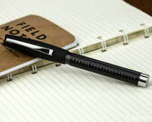 Faber-Castell Essentio Black Leather Fountain Pen - Closed on Notebook