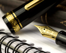 Sailor 1911 Large Fountain Pen - Black with Gold Trim - Nib on Notebook