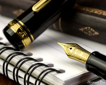 Sailor 1911 Realo Fountain Pen - Black with Gold Trim - Nib on Notebook