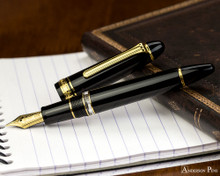 Sailor 1911 Realo Fountain Pen - Black with Gold Trim - Open on Notebook