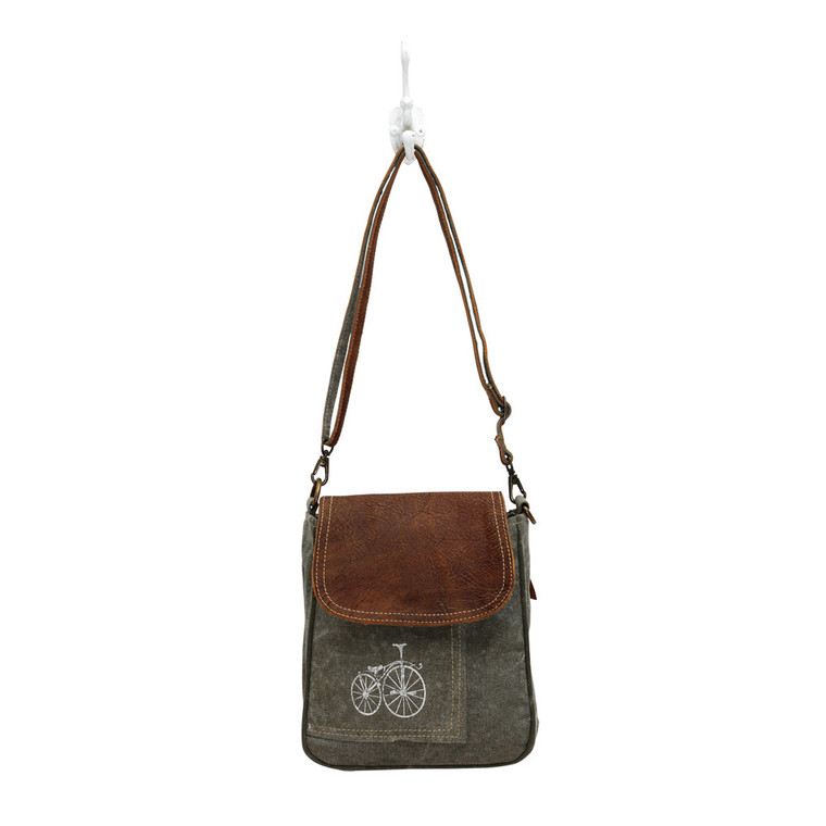 This bicycle print shoulder bag is crafted from quality with a combination upcycled canvas & leather. It has a premium leather flapover and a zipper pocket at the backside.