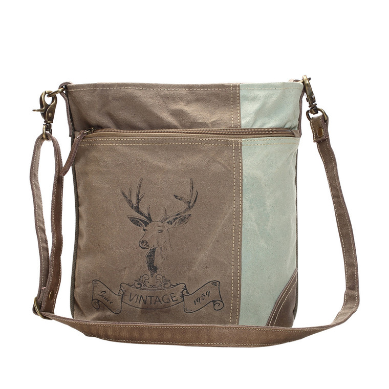 This deer print shoulder bag comes with a large front zipper pocket and a detachable strap. Its made up of canvas with a zipper top closure. Made of upcycled canvas and leather.
