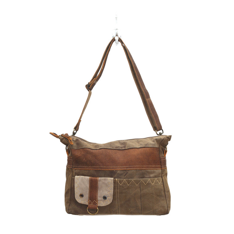 As the name suggests, this bag calls for a perfect adventure. This features two front pocket as well as a Flap-over closure. Made of upcycled canvas and leather.