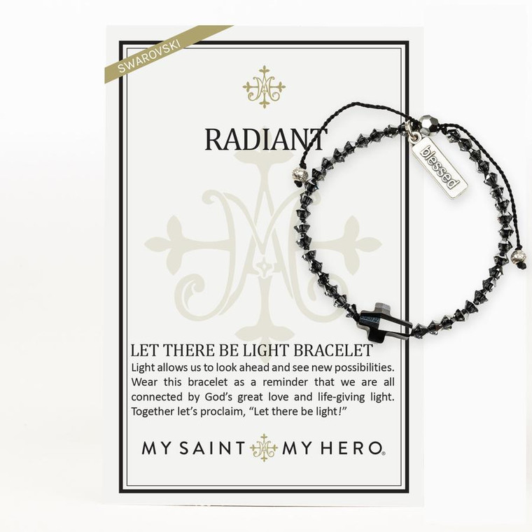 """RADIANT  Light allows us to look ahead and see new possibilities. Wear this bracelet as a reminder that we are all connected by God's great love and life-giving light. Together let's proclaim, """"Let there be light!""""  Adjustable cording which opens to 9"""" diameter Silver Night Swarovski beads, crystal cross, silver-tone """"blessed"""" tag Medals made in Italy On an inspirational card"""